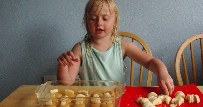 Una niña cocinando galletas con plátano