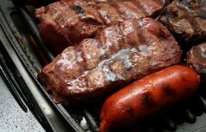 Una parrilla con carne y chorizos asados