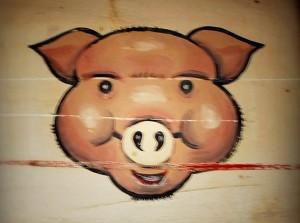 Cabeza de cerdo pintada en una madera