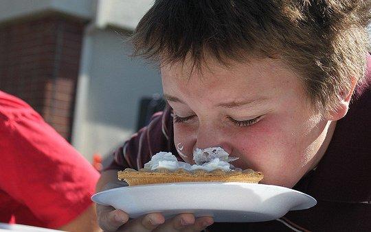 Niño comiendo tarta en un comedor escolar