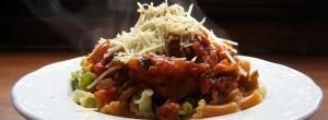 Un plato de macarrones con tomate echando humo