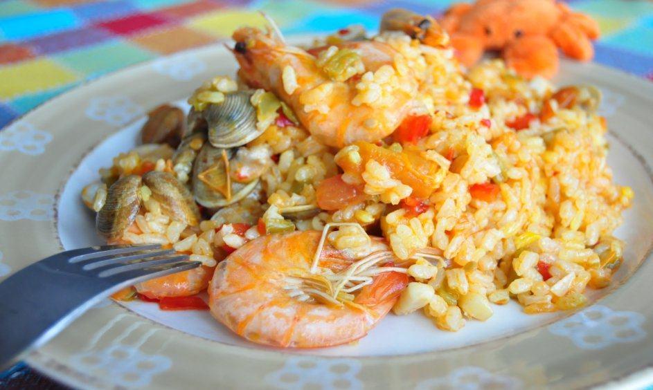 Paella marinera en su plato, con langostinos, calamares y chirlas