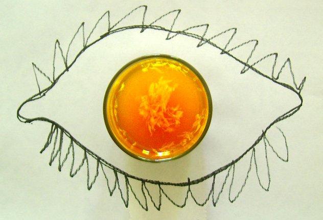 Un baso de zumo de naranja sobre un dibujo de un ojo