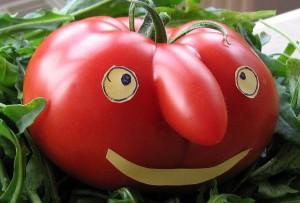 Un tomate sonriendo, con ojos y boca hechos de papel