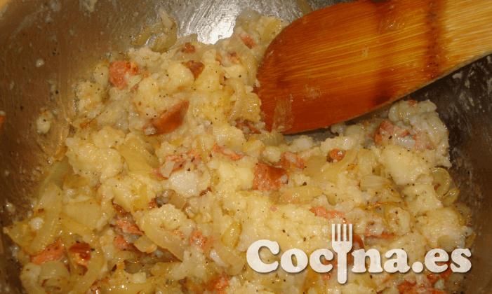 Elaboracion de los huevos sobre lecho de patata chorizo y cebolla